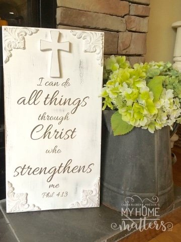 white distressed background with brown lettering and applique's applied; script font is called Allura